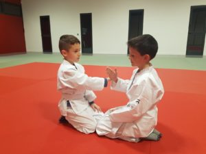 Deux enfants à genoux sur le tatamis s'entrainant à l'aïkido mains nues