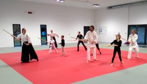Groupe d'aikidoka inter-générationnel sur le tatamis exécutant des mouvements avec jo